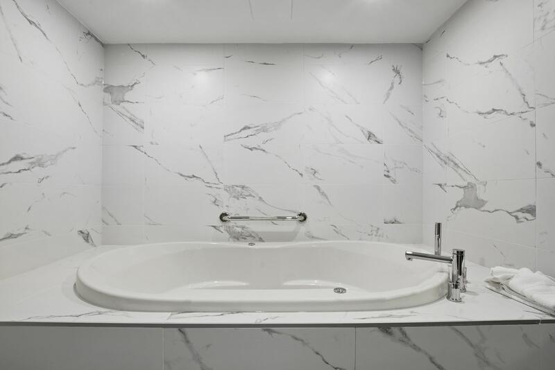 bathtub with marble walls