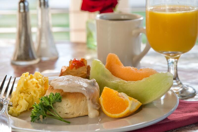 Breakfast plate with a biscuit and gravy, eggs, fruit and orange