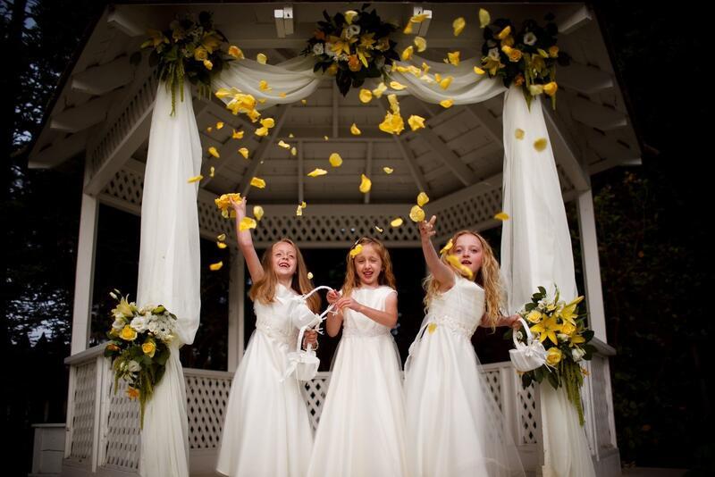 Flower girls tossing flowers in a wedding gazebo