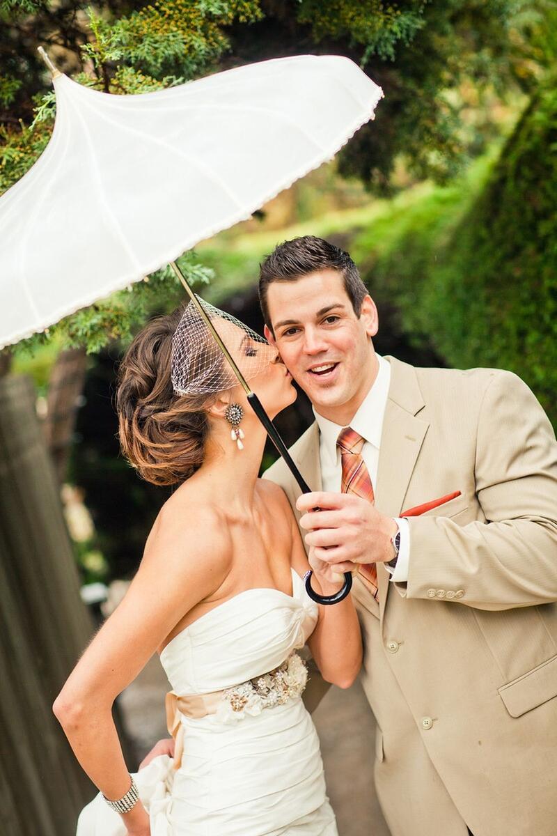 Bride kissing groom under an umbrella