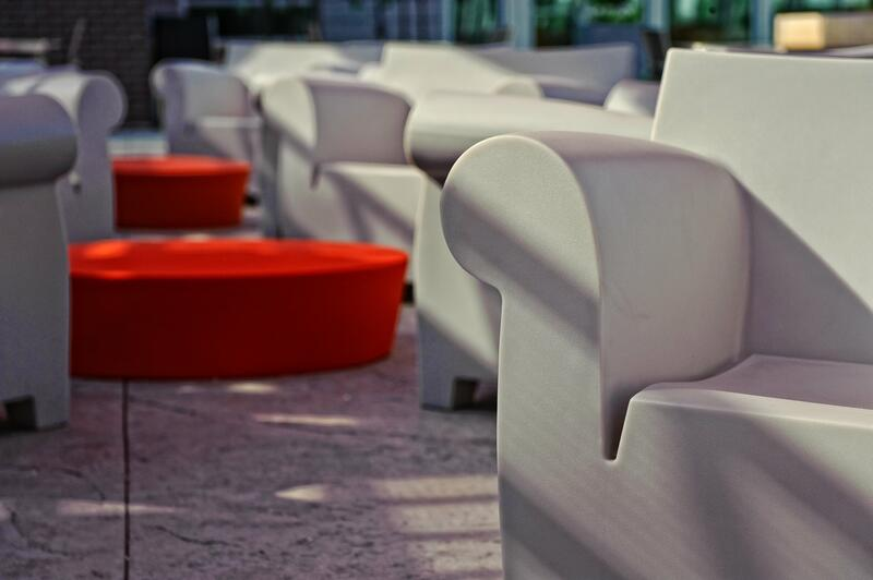 Close photo of grey chair and red tables