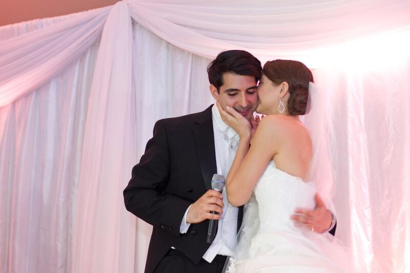 a bride whispers in her grooms ear