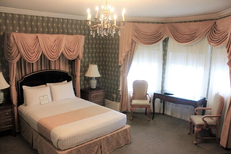 Room with Queen bed, chandelier, sitting chairs