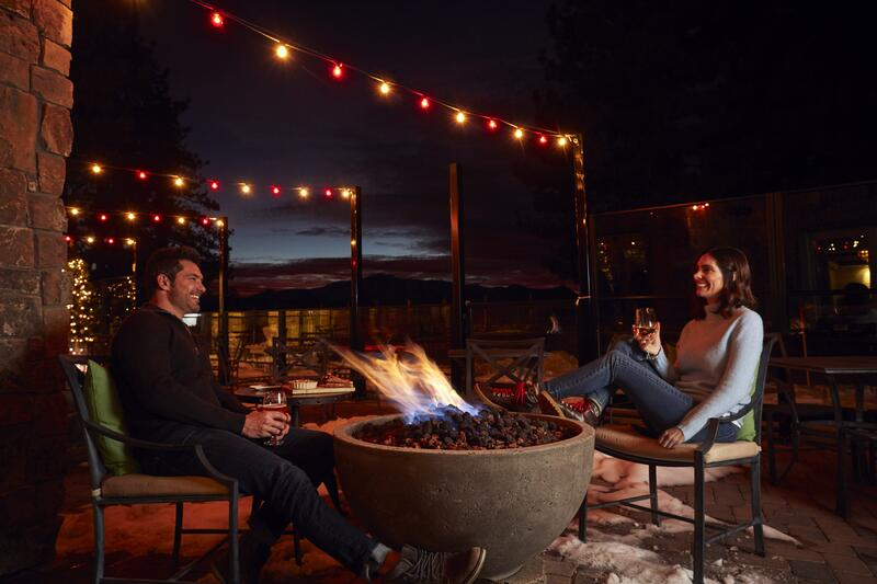 Couple sitting by fire pit at night