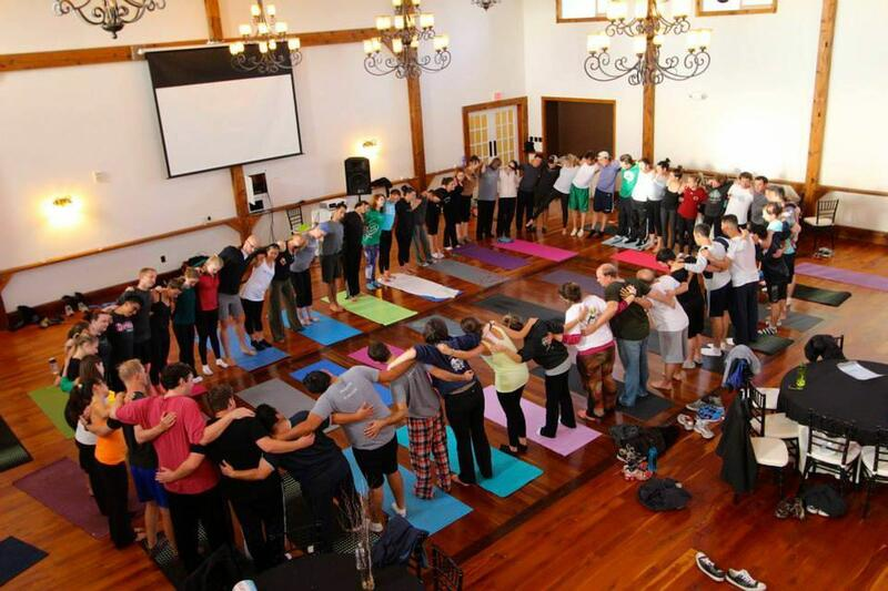People standing in a room around yoga mats.