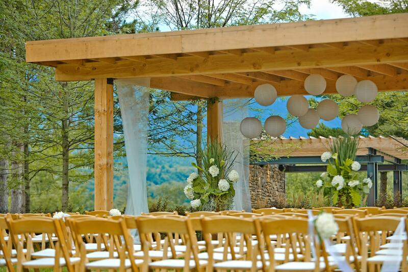 Lines of chairs for wedding seating, leading to a pergola.
