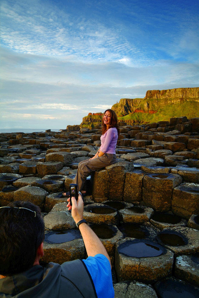 Woman Sitting On Basalt Columns Of The Giants Causeway