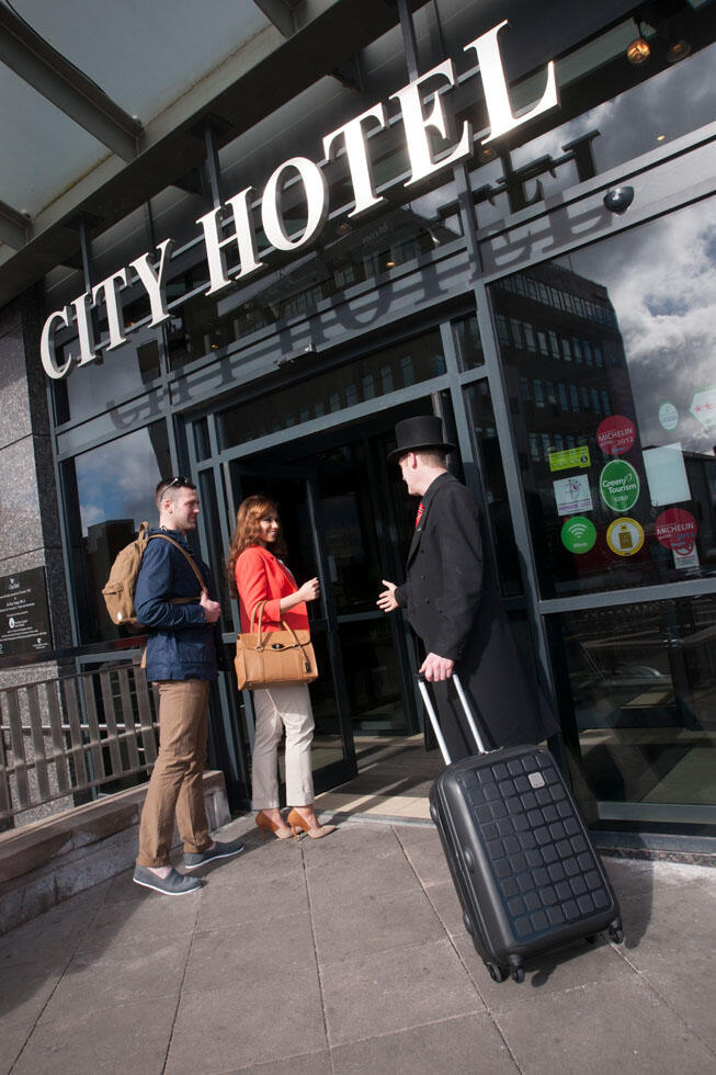 Couple And Doorman At The Entrance To City Hotel Derry