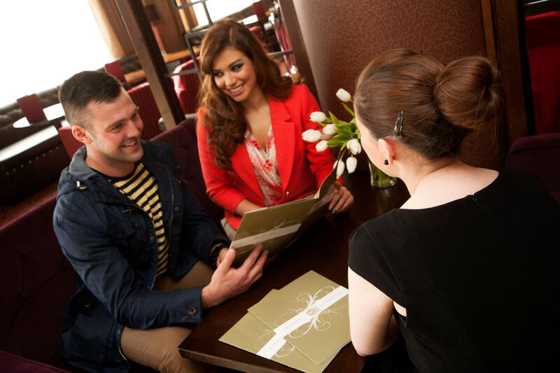 Couple And Woman Looking At Event Planning At City Hotel Derry