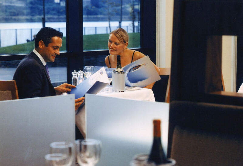 Couple Looking At Menus In Restaurant At City Hotel Derry