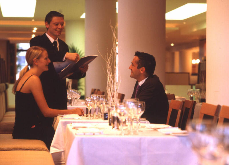 Waiter Handing Menus To A Couple In Restaurant At City Hotel Der