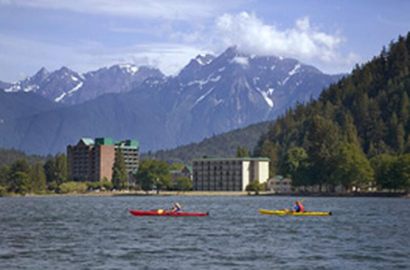 Two kayakers with view of hotel and mountains in the background.