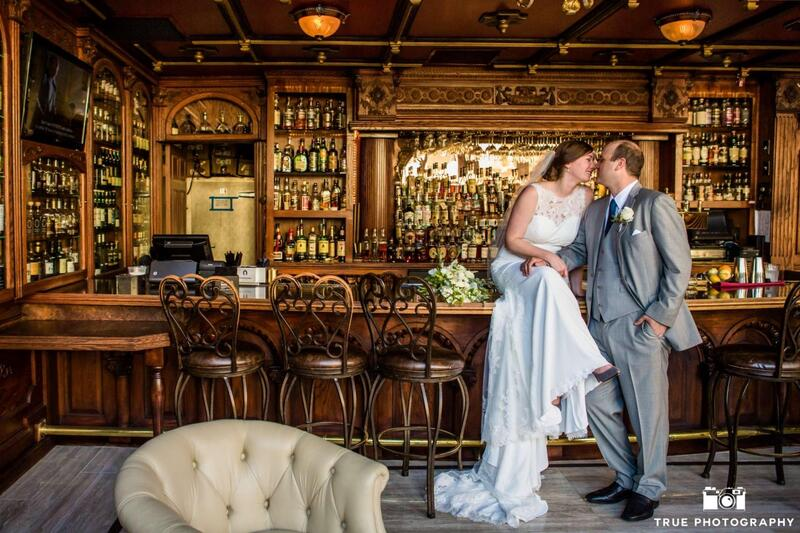 bride and groom kissing on bar