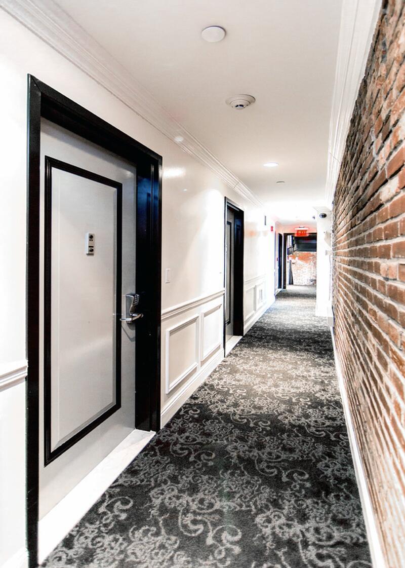 Hotel hallway with brick wall.