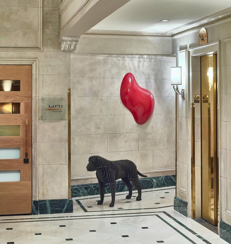 Lobby with dog statue and art next to gold elevator.