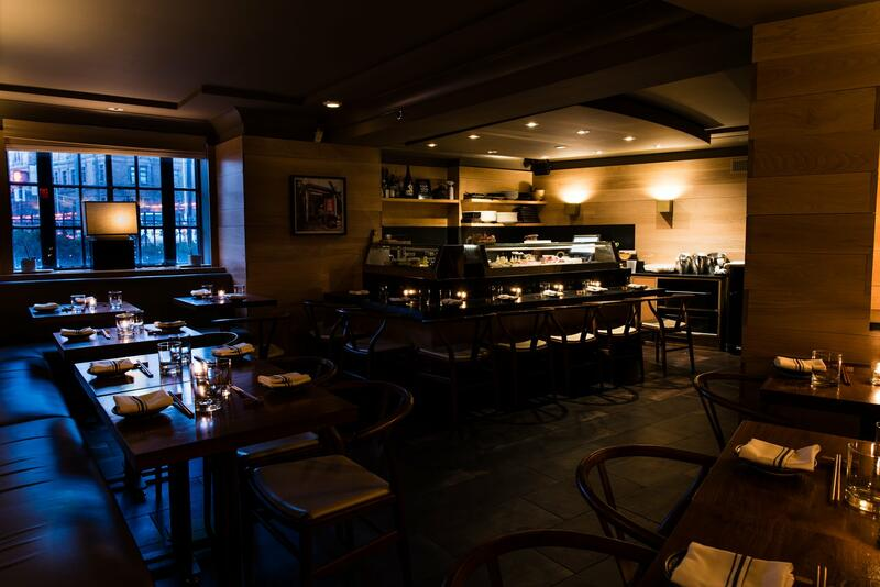 Dimly lit restaurant tables with place settings and sushi bar