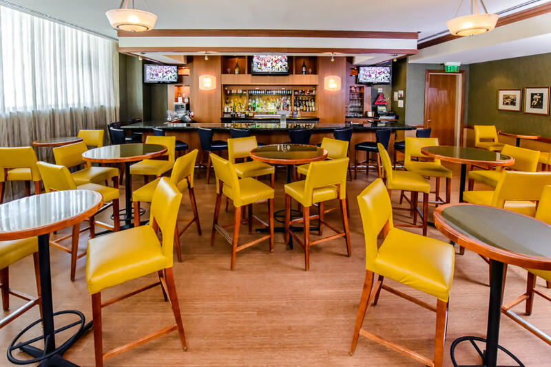 high top circular tables with yellow bar stools