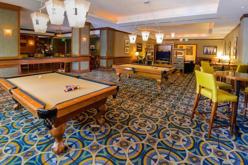 two pool tables next to high top circular tables with yellow bar