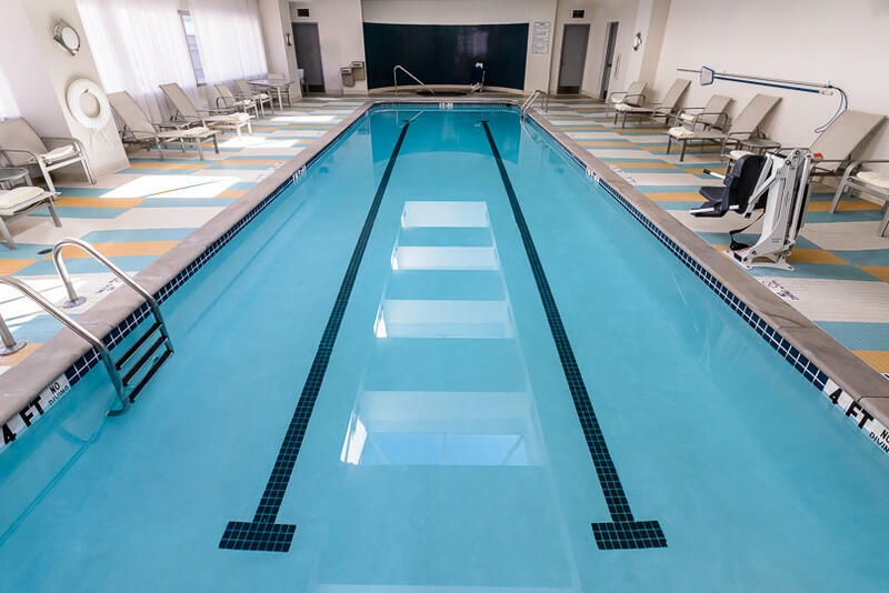indoor pool with pool chairs bordering the walls
