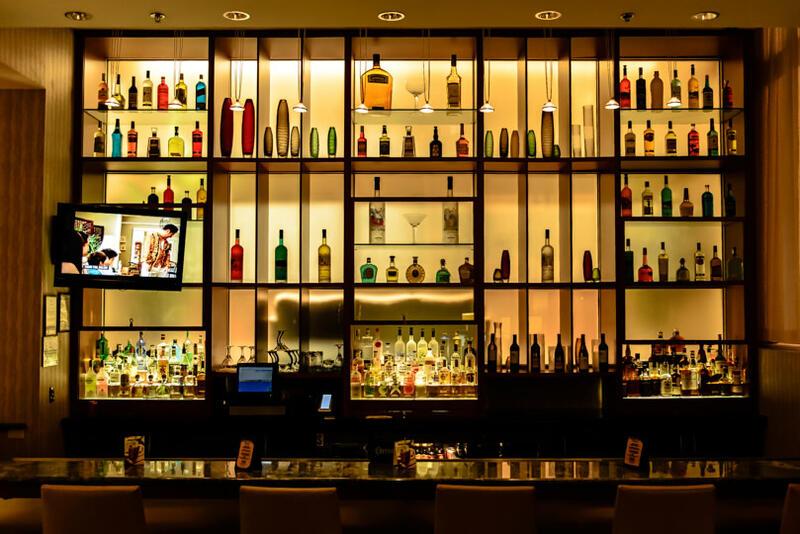lit bar with liquor bottles on shelves