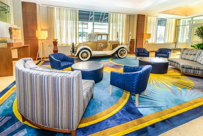 small sofas and chairs next to vintage car in lobby