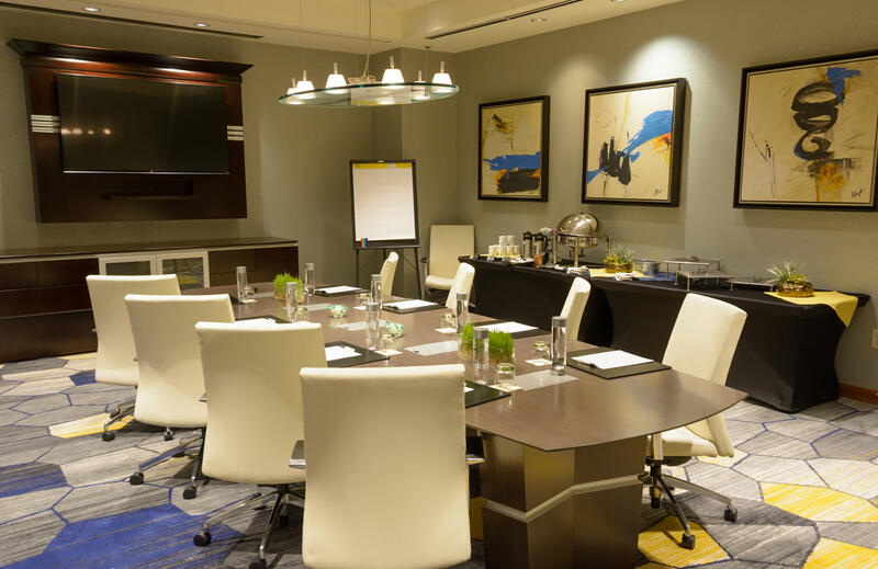 meeting room with white rolling chairs and table for 8