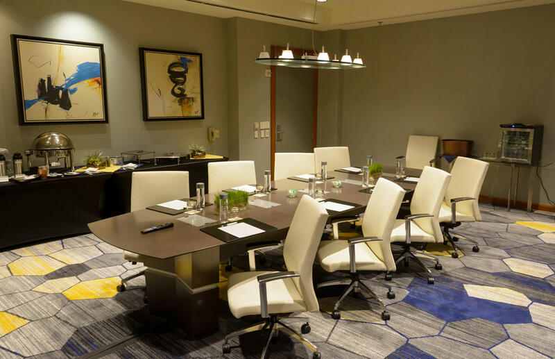 meeting room with white rolling chairs and table for 9