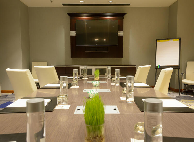 meeting room with white rolling chairs and table for 10