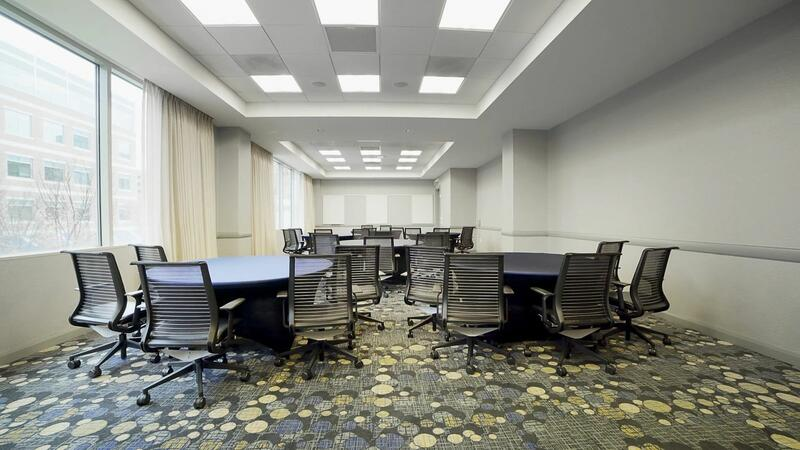conference room with three circular tables and rolling chairs