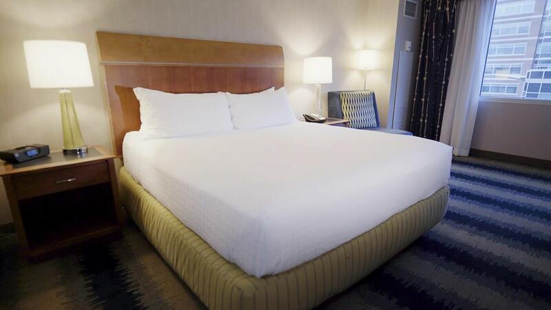 room with king bed, two nightstands and a seating chair next to