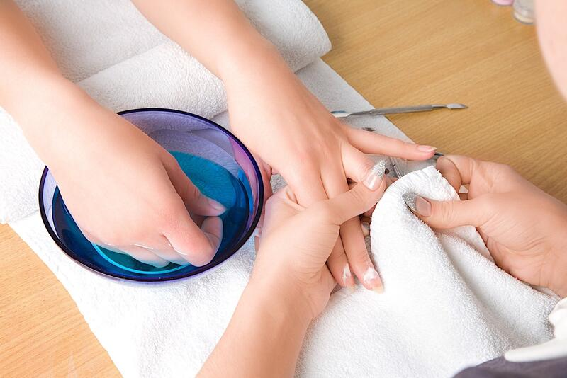 Close photo of hand receiving manicure.