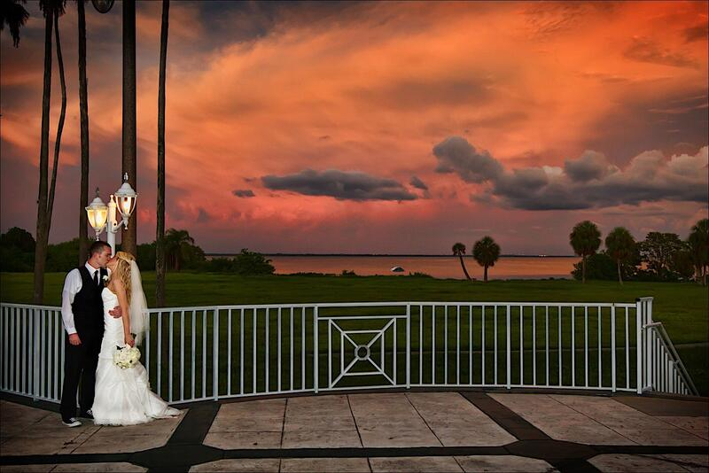 Newlyweds kissing at sunset with Tampa Bay in the background.