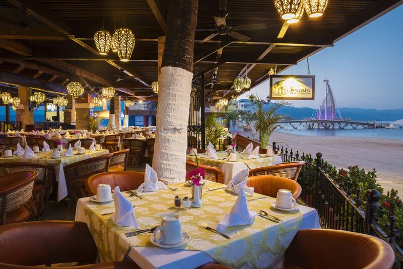 dining tables under canopy near beach sand