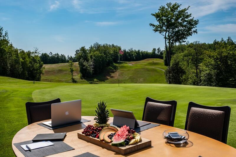 Table with laptops and fruit on golf course