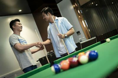 two guys shaking hands before pool game