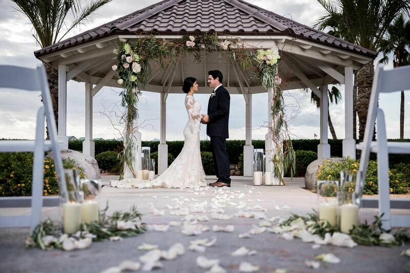 Newlyweds embracing under gazebo.