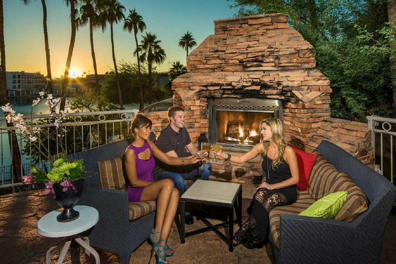 Friends enjoying cocktails near outdoor fireplace.