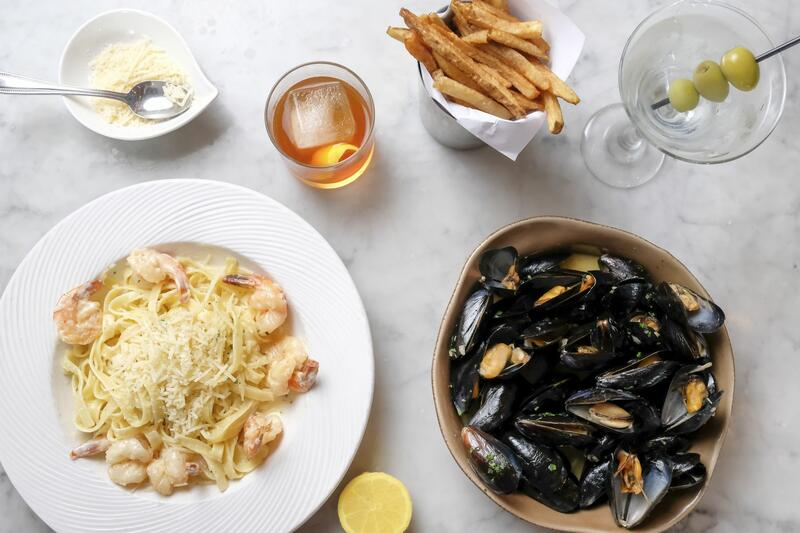 plate of seafood pasta and mussells, french fries and two cockta