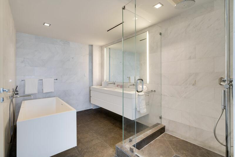 bathroom with white bathtub, walkin shower and large white vanit