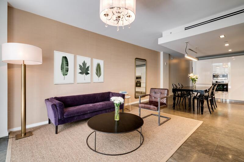 living room with purple velvet sofa and round coffee table