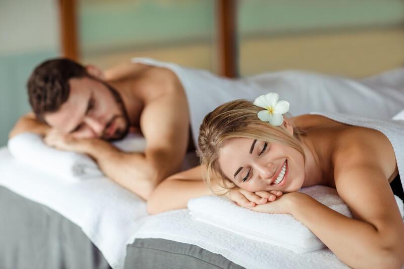 Couple having massage and smiling brightly at Amatara Wellness R