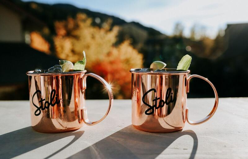 Moscow mules in copper mugs with mountainscape background.