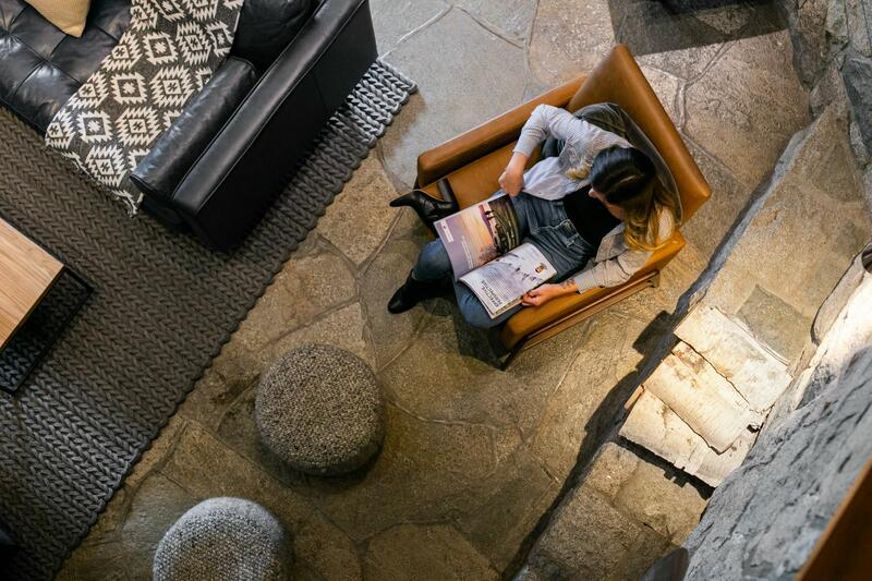 Overhead photo of woman reading in a lush lobby.