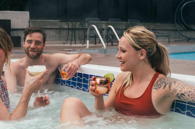 Friends enjoying cocktails in a hot tub.