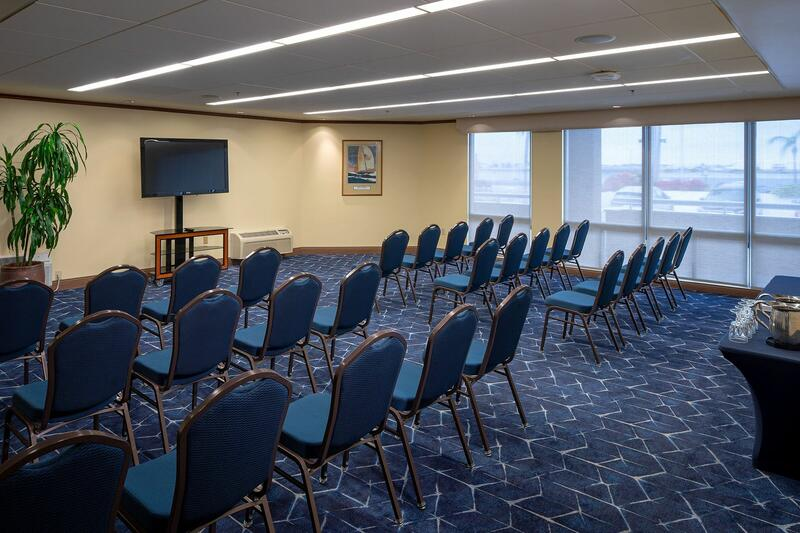 Three rows of chairs facing a TV screen in hotel meeting space