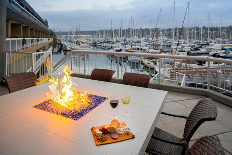 Wine and cheese platter on a fire table overlooking a marina