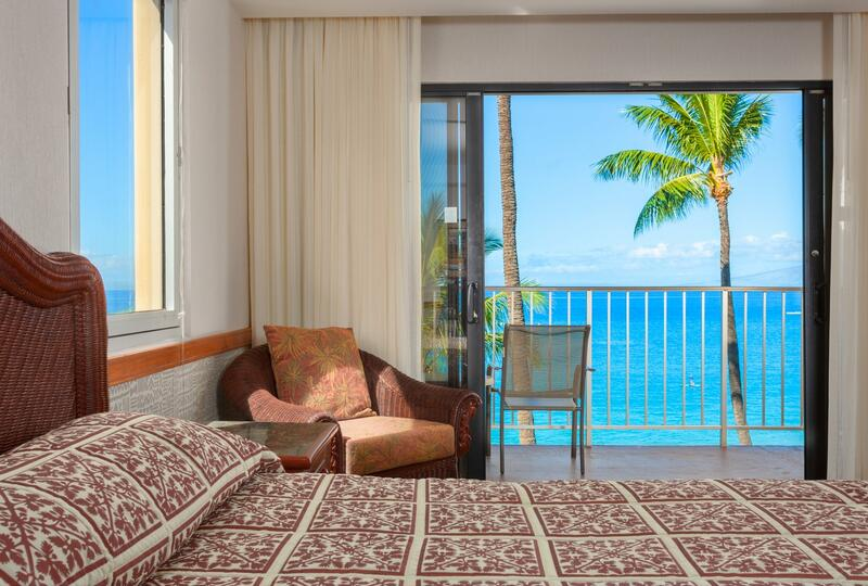 bed in hotel room with balcony overlooking beach and palm tree