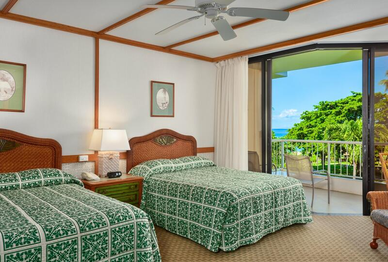 two beds in hotel room with balcony overlooking beach and trees