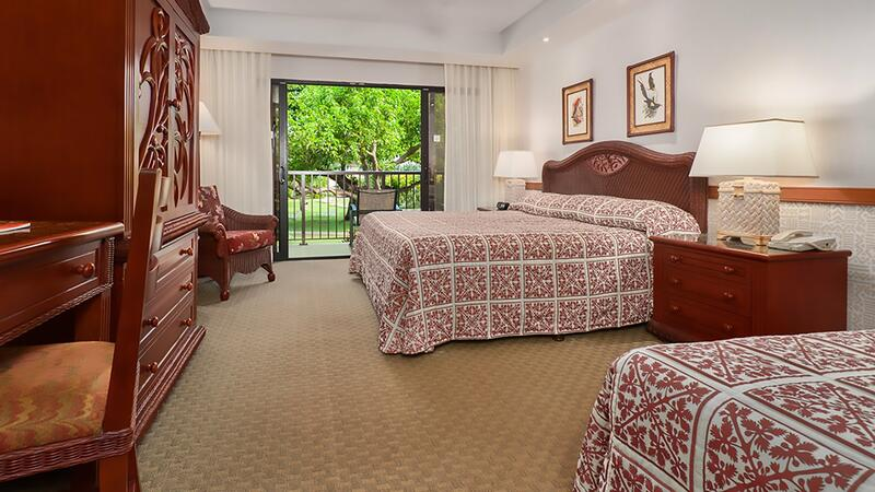 two beds in hotel room with balcony overlooking trees