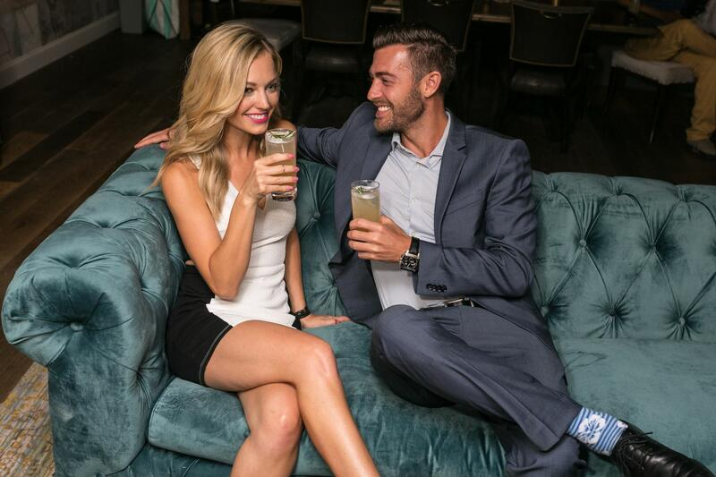 couple smiling and drinking on green couch